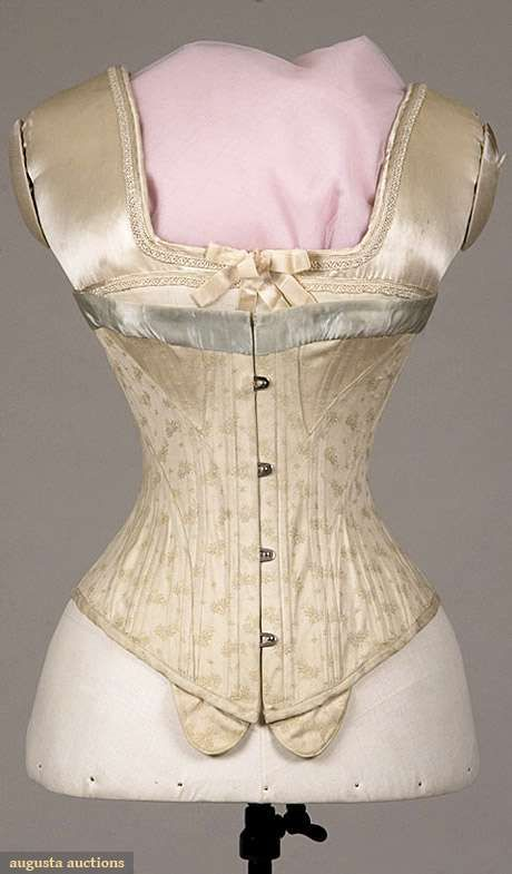 "COTTON BROCADE S-SILHOUETTE CORSET, 1900-1910 Cream cotton w/ small blue & yellow faded flowers, steel busk, blue silk satin ribbon trimmed top, corset pieced to push upper torso forward, attached tabs below busk for pin-on garters, B 28.5+"", W 20+"", CFL 11.25"", (few worn spots in blue ribbon) good"