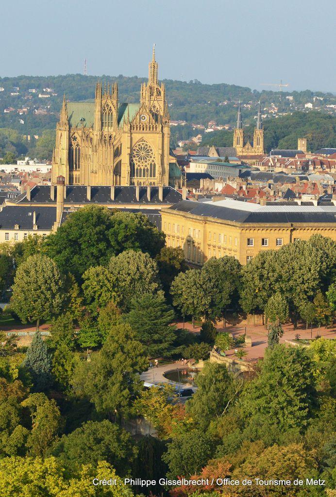 Metz vu du ciel  (25) | A l'avant plan, la végétation du jardin de l'Esplanade et du plan d'eau. Le palais de justice est visible au second plan sur la droite, ainsi que la toiture de l'Abbaye St Arnould (aujourd'hui Mess des Officiers). Surpassant l'ensemble, la Cathédrale St Etienne. Les deux petites tours de l'église Ste Ségolène, et à leur droite, la tour carré de l'Hôtel St Livier, se trouvent sur la Colline Ste Croix, berceau de la ville de Metz.  Découvrez M...