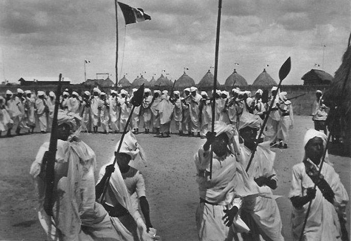 Dubat warriors assemble before the Italian flag in their camp.