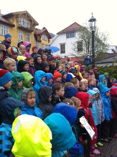 130 eight-year olds singing in gushing rain. Lots of spectators, lots of humour, a joyful experience! Kragerø in Norway. Photo: Mette K. Ofstad