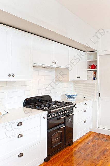 Kitchen 399 by Sally Steer Design. Wellington. NZ. Cup pull handles on drawers, knobs on doors and recessed handle on sliding pantry door.