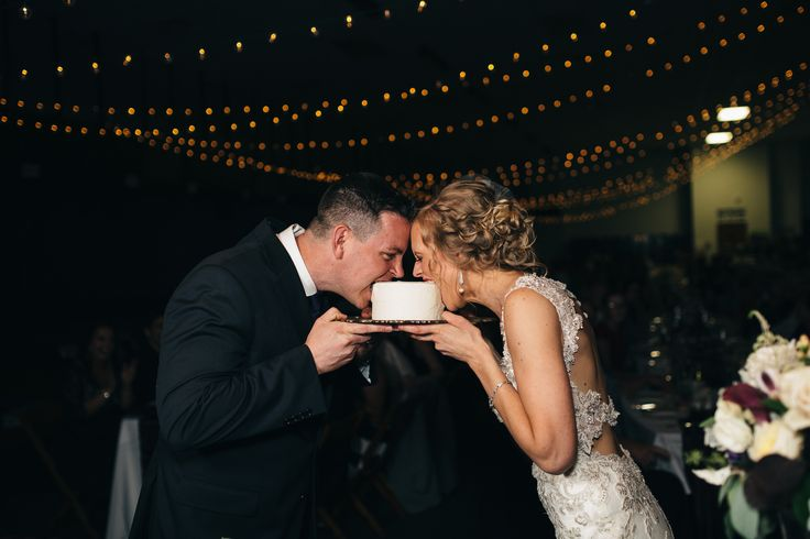 Bride and groom cut cake at wedding reception in Fremont, Ohio. —  Lace Back Detail Wedding Dress: Maggie Sottero - Jade  —  Grey Suit: Men's Wearhouse  —  Bridal Earrings from BHLDN: Spire Earrings by Ben Amun in Pearl  —  Photography: Swatch Studios http://www.swatch-studios.com/