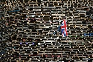 A Loyalist youth climbs wooden pallets constructed for the 11th night bonfire at the New Mossley estate in Belfast, Northern Ireland. Tradition holds that the bonfires commemorate the lighting of fires on the hills to help Williamite ships navigate through Belfast Lough at night when Protestant King William III and his forces landed at Carrickfergus to fight the Catholic Jacobites, supporters of the exiled Catholic King James II.
