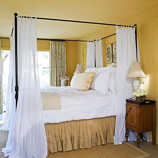 Soothing PaletteGoldenrod hues bathe this bedroom in warm, cheerful color. Painting both the walls and the ceiling with the sunny yellow hue creates a continuous look from floor to ceiling. The black iron four-poster, draped with wispy white linens, adds contrast to the room's light palette. A burlap bed skirt and grass-cloth area rug add a splash of natural texture.
