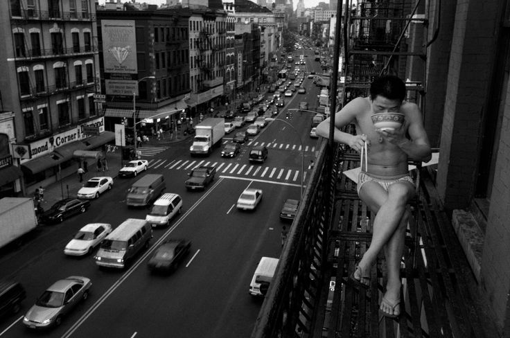 Chien-Chi Chang USA. New York City. 1998. A newly arrived immigrant eats noodles on a fire escape.