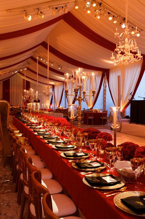 Red and white striped draping, crystal chandeliers and candelabras make for a classic wedding tent.