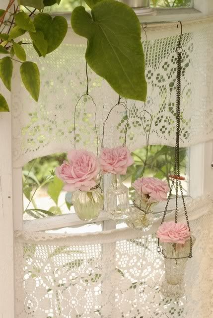 Lace curtains and hanging perfume bottles with flowers look so pretty
