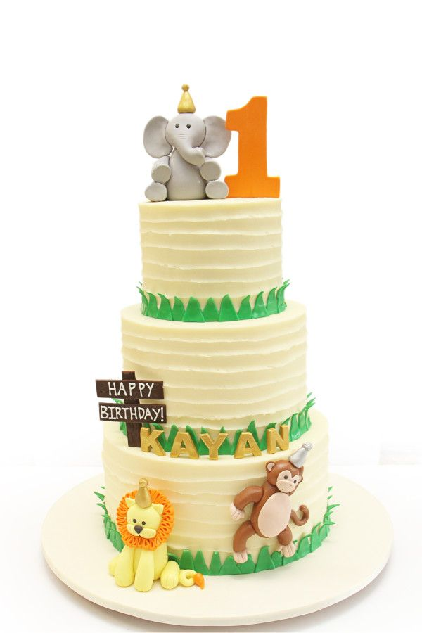 Vertically striped buttercream first birthday cake. Animals include lion, monkey and elephant. Happy Birthday Kayan!