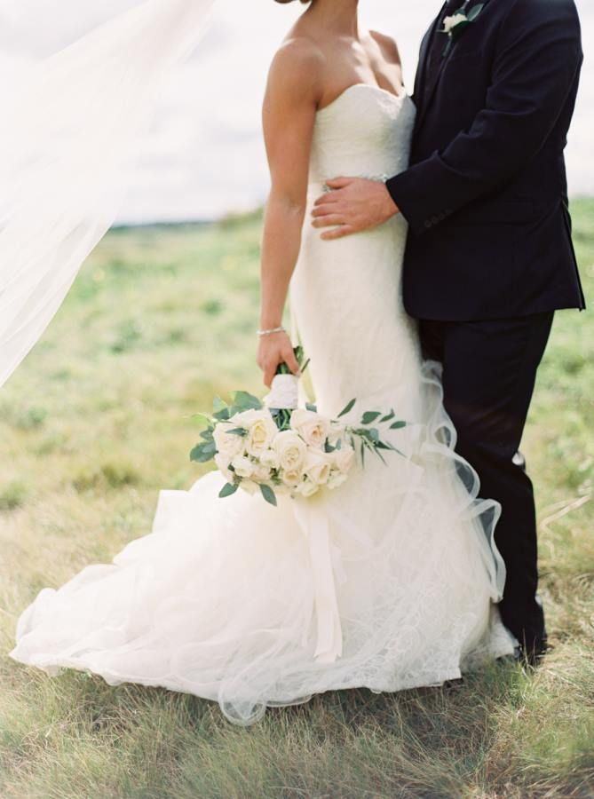 We're in love with this romantic trumpet wedding dress and all white wedding bouquet.