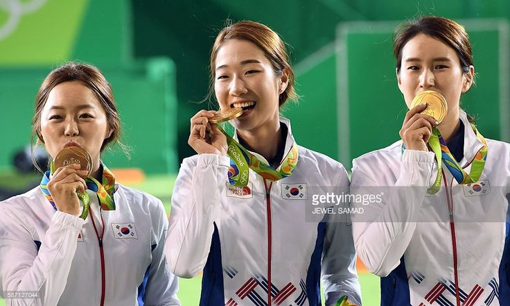 South Koreas archers Hyejin Chang, Misun Choi and Bobae ki kiss their gold medals during the medal ceremony at the end of the Rio 2016 Olympic Games Women's Team competition at the Sambodromo archery venue in Rio de Janeiro, Brazil on August 7, 2016. South Korea defated Russia to win the gold. Taipei won the bronze. / AFP / Jewel SAMAD