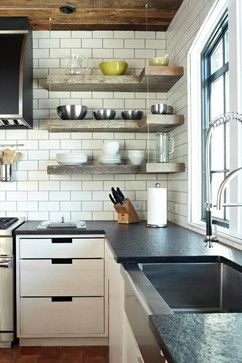 White cabinets, white subway tile, black countertops, undermount stainless sink, open timer shelves, no uppers, black metal windows. I love all of it.