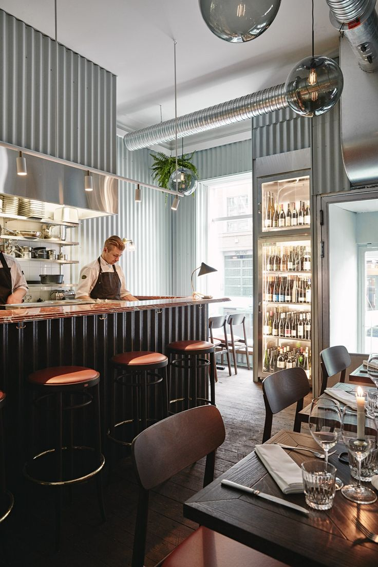 Joanna Laajisto has combined mint-coloured corrugated metal wall panels with red-orange marble furniture inside this restaurant in Helsinki