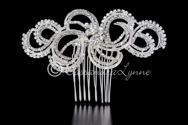 This wedding hair comb has a modern feel with dozens of clear rhinestone embellishing delicate swirls. The center has several larger rhinestone jewels for extra sparkle. It is 4.25 inches long and 1.7