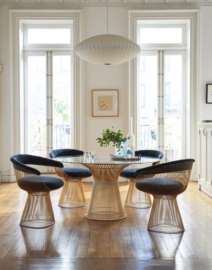 Warren Platner chairs in navy velvet and a modern chandelier