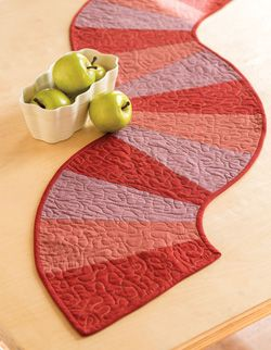 This versatile quilted table runner is easy to make and would look beautiful on any table top. This table runner called Wave Runners features wedges.