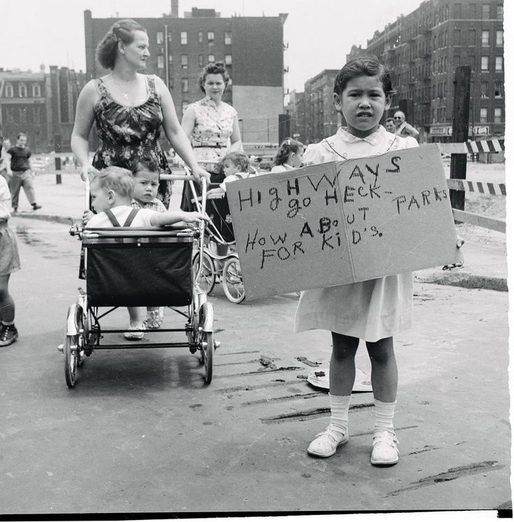 """United States, 1950s  Marchers protest cave-in tragedy. Six-year-old Dolores Siat (of 714 Grand Avenue, Brooklyn) holds placard as she marches along with her mother (background) in neighborhood protest demonstration, June 13. The mother's march was a """"show of compassion"""" demonstration after six children were killed in a cave-in while playing in a deep excavation in the Williamsburg section of Brooklyn."""