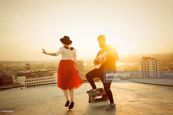 dancing on the roof,man playing the guitar and the woman dancing under the nice warm light of the sun