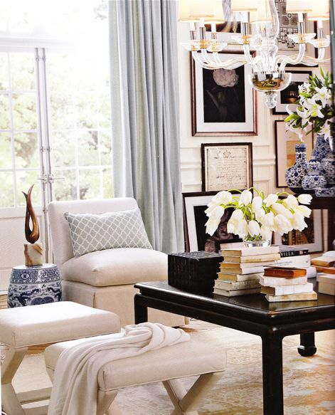 beautiful styling.  white slipper chair and x benches, lucite chandelier, black lacquer coffee table, gallery wall, and asian accent pieces.