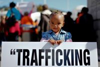 """""""In today's globalized world, the risks of human trafficking in supply chains are significant throughout economic sectors and affect all States"""" - UN human rights expert Joy Ngozi Ezeilo.    (PHOTO: A South African child holds a poster during an anti-human trafficking protest © EPA/NIC BOTHMA)"""