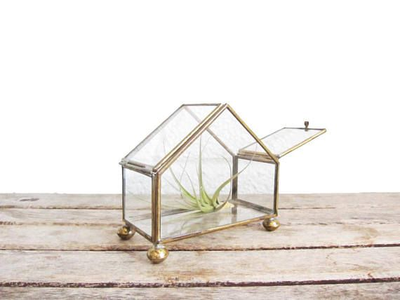 This vintage brass and glass tabletop display case features a lovely house shape, two hinged top doors, and beautiful glass panels. It stands 3.75 tall and measures about 4 across, and about 2 deep. The gold colored bass edge work is eye-catching and lovely; it would make a gorgeous curio cabinet for small figurines, as a jewelry display, or as a desktop greenhouse for tiny air plants or succulents. Stands on four round brass feet. In fantastic condition with no notable wear other than minor…