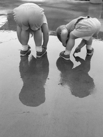 Two Kids Bending Over Playing in Mud Puddle Valokuvavedos