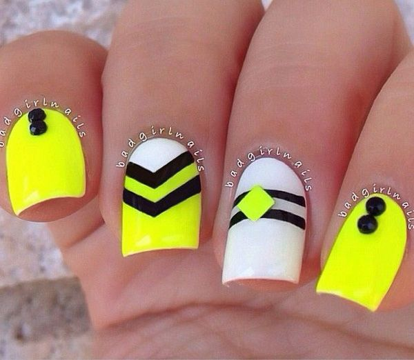 A cute and simple yellow themed nail art design.  The design gives each nail different striped designs in alternate colors. Embellishments are then added on top for more effect.
