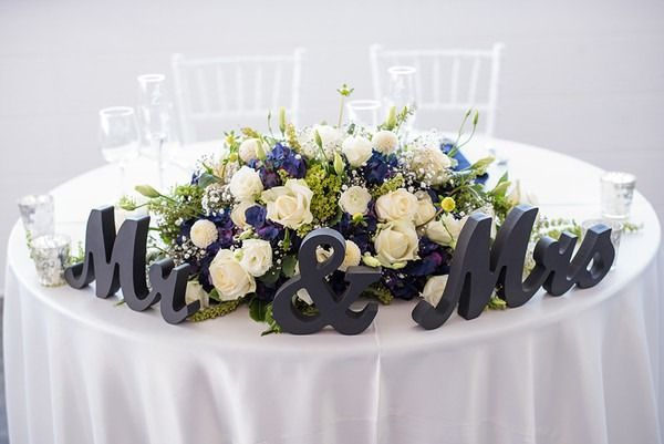 """Spring wedding sweetheart table idea - blue + ivory flower arrangement with navy blue """"Mr."""" and """"Mrs."""" wooden cutout signs {Holly D Photography}"""