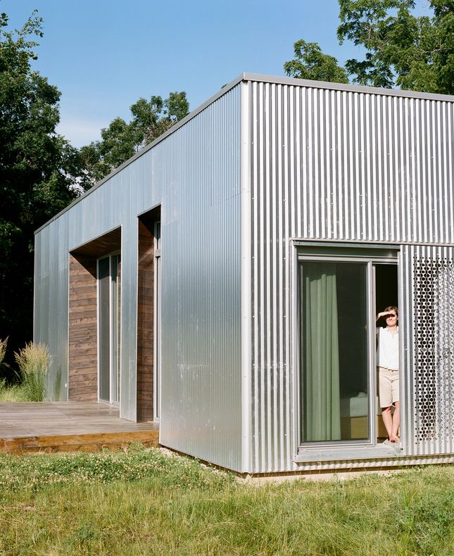 Hints of the interior wood palette are visible from outside the house, creating a rich edge for the corrugated metal facade. Perforations in the metal near the sleeping quarters help bring extra light inside and cast elegant patterns in shadow.