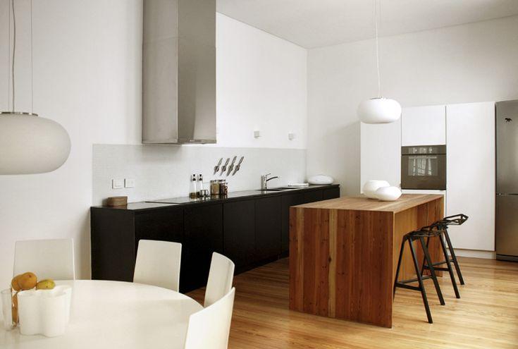 Black base cabinets, white upper cabinets tall cabinets , timber grain island, white splashback walls.