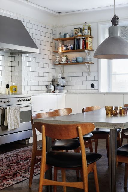 white brick tiles, range cooker, lamp shade, mid century chairs and polished concrete table top...