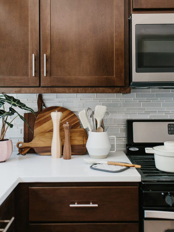 Styling Our Rental Kitchen Two Ways : Color vs Neutrals || Neutral Kitchen Styling with Wood boards, trays, and candlesticks and a pop of blush pink in the planter.