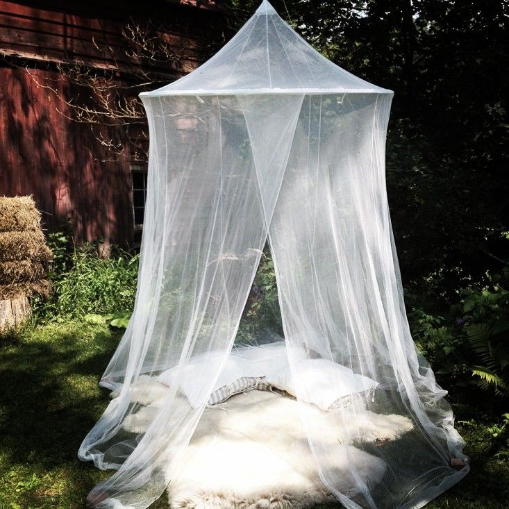 Mosquito net tent with sheepskin rugs by Hilary Robertson