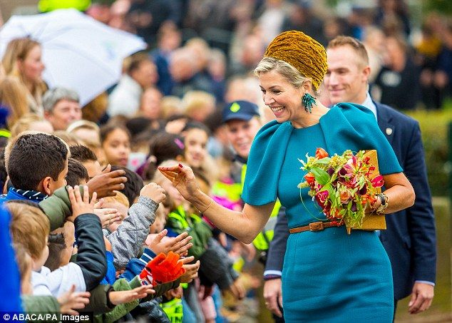The Netherlands' Queen Maxima, 45, made a style statement on a visit to Almelo and Northeast Twente, wearing an unusual mustard velvet turban, elaborate earrings and a mohair coat.