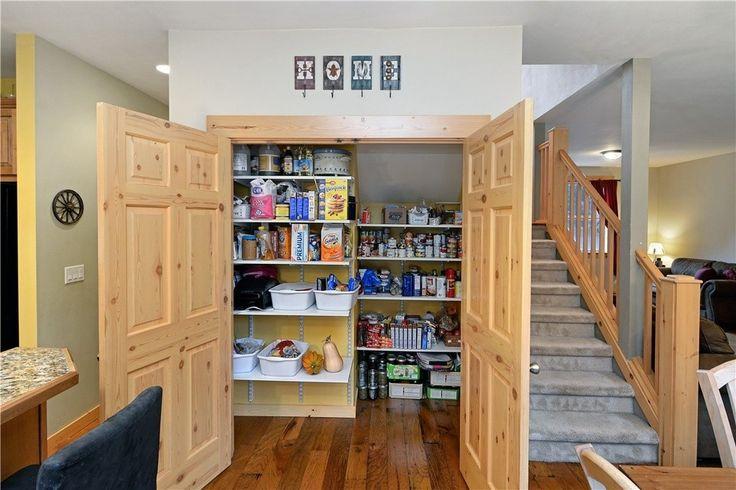 Dieses ist eine großzügige Art von begehbaren Speisekammer neben gebaut und erweitert unter der Treppe. Es hat breite Doppeltüren und ein paar Regale montiert.