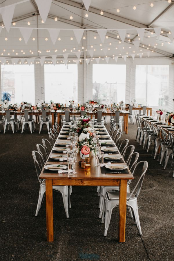 tent wedding decor, white bunting and string lighting for the ceiling | harvest tables paired with metal cafe chairs | casual chic modern rustic tented wedding reception in the city | modern boho wedding