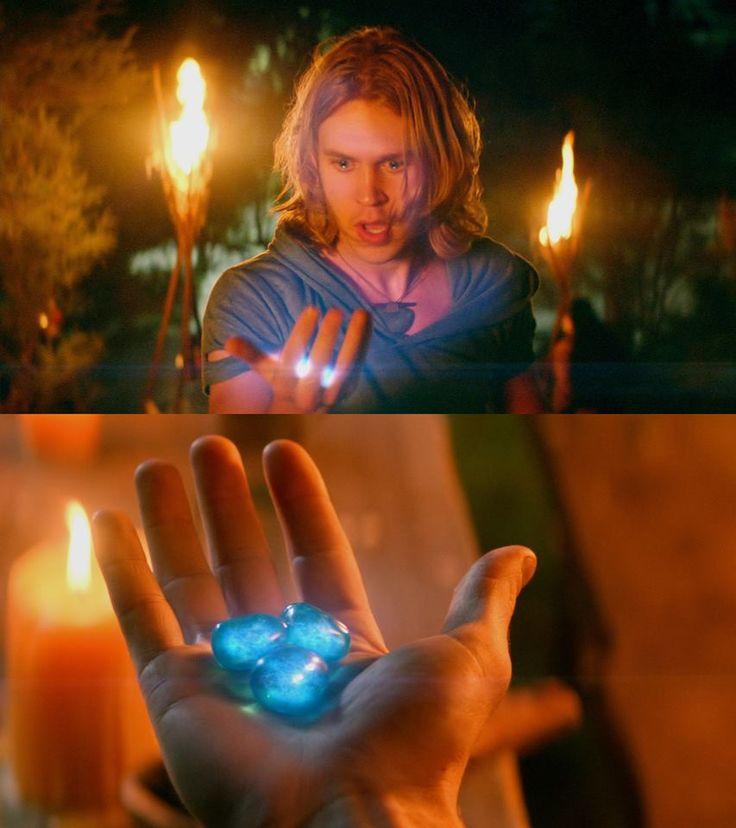Jake Evans con el pelo largo, descubriendo el secreto de una piedra mágica. (The Shannara Chronicles)