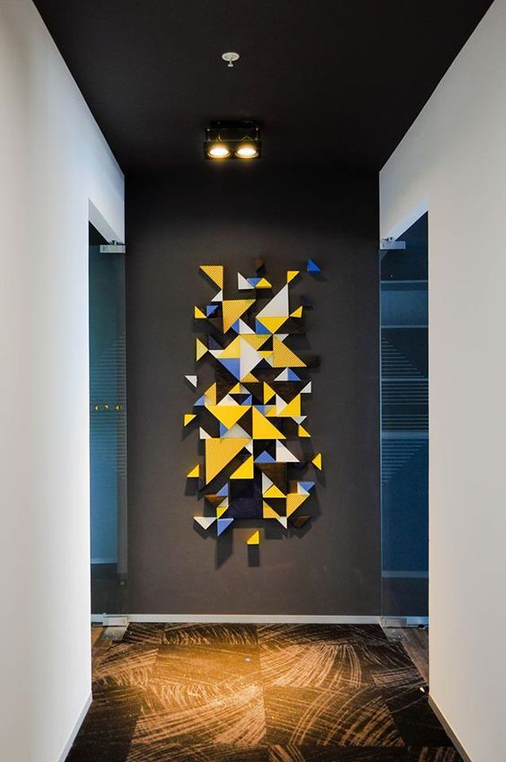Iluminação direta: luminária de sobrepor (fixada na laje, não é embutida no forro) direcionando a luz para a parede com escultura. Projeto de Oxigeno Arquitectura