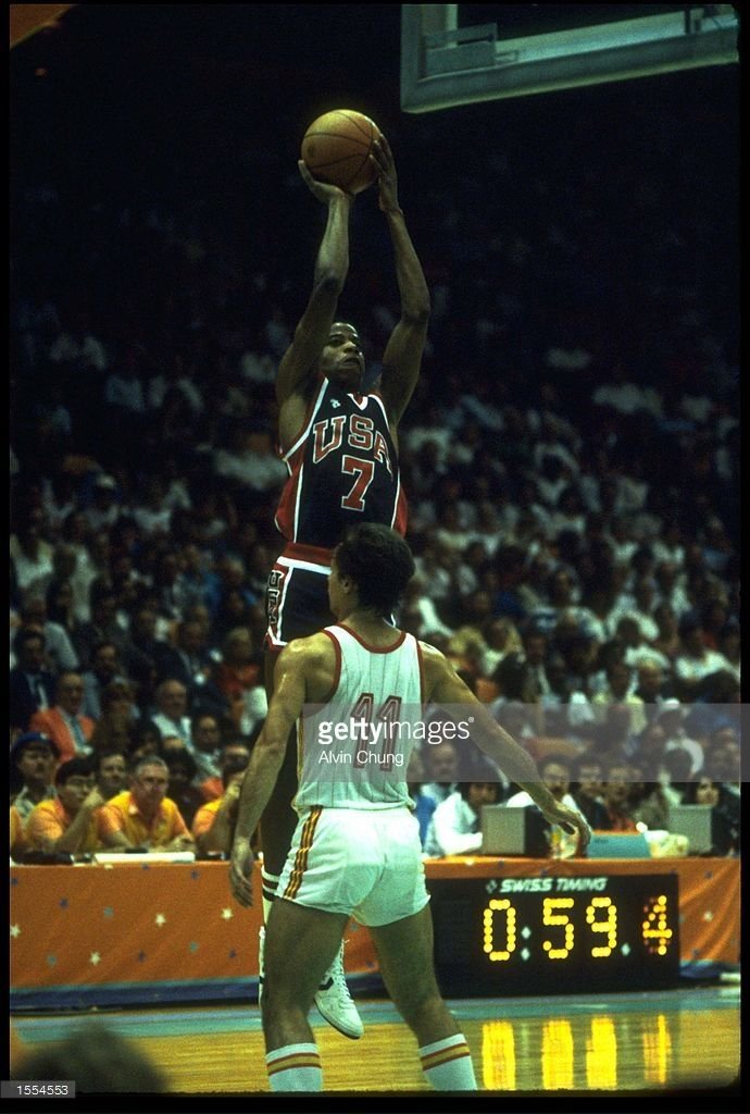 VERN FLEMMING OF THE UNITED STATES TAKES A JUMP SHOT OVER A SPANISH DEFENDER DURING THEIR MATCH IN THE 1984 LOS ANGELES OLYMPICS BASKETBALL FINAL. THE USA TEAM WON THE GOLD MEDAL WITH AN IMPRESSIVE 96-65 SCORE OVER SPAIN.