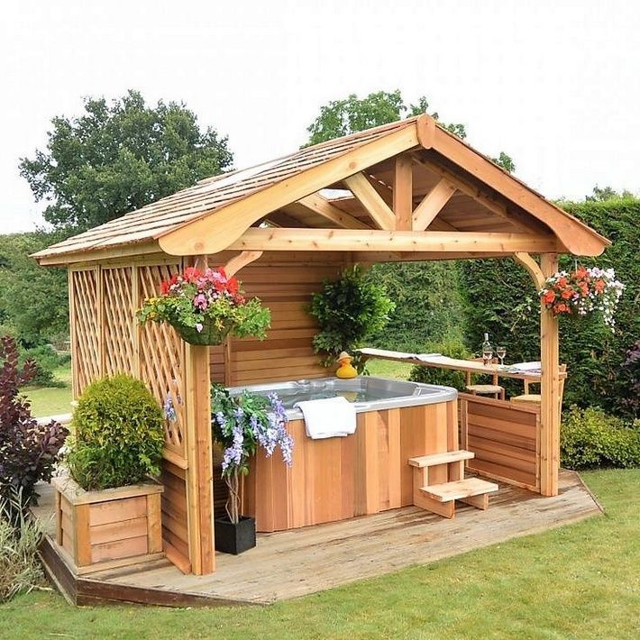 This wooden cottage themed hot tub depicts the rustic country side theme. The cottage is set on a wooden platform in the garden and has fence on one side and a nice compact bar on the other. The hanging flower baskets and colorful and bright flowery planters take you into fantasy and dream world. #modernpoolandspa
