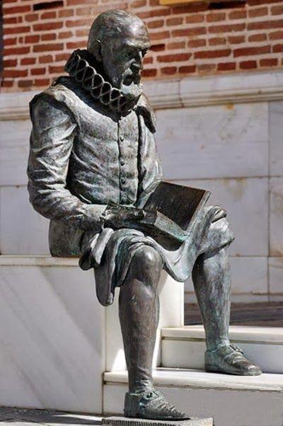 Estatua de Miguel de Cervantes, sentado acabando su libro