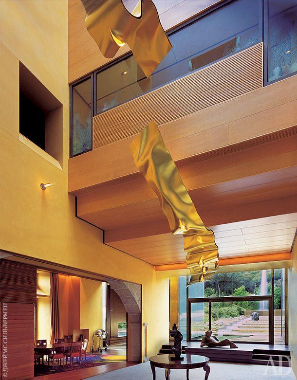 Внутреннее патио сосветильником Инго Маурера. На столике— скульптура Фернандо Ботеро. Фигура лежащего человека— работа Франсиско Лейро.