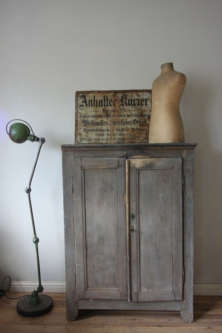 lovely cabinet with vintage sign and little model, love the old lamp and the simple white background.xx