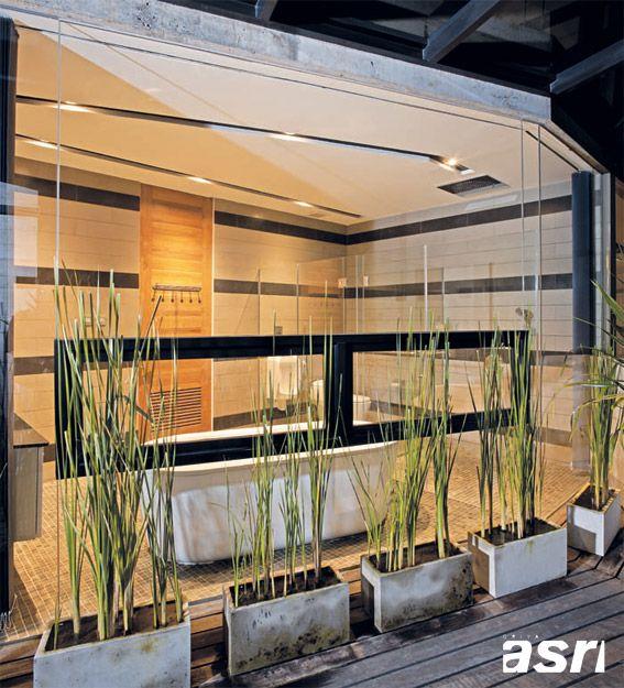 Kamar mandi utama dengan saniter bergaya modern dan dinding kaca lebar ini menyajikan tempat berbilas ataupun berendam yang santai