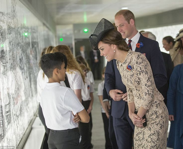Prince William and Kate Middleton speak to a schoolboy as they walk through the visitor centre at the First World War memorial