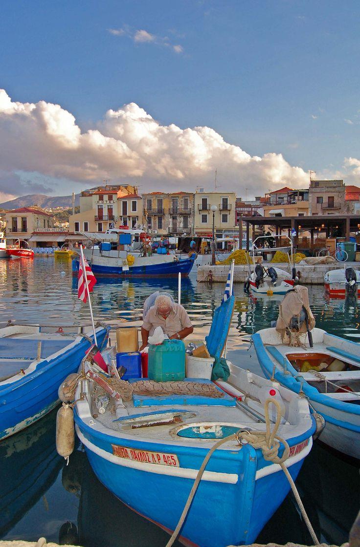 Een visser bezig op zijn grieksblauwe vissersbootje met het opruimen van zijn spullen aan het einde van de dag na een dag vissen, een mooi uitzicht over de in ,typische griekse kleuren, oude venetiaanse haven van Rethymnon op Kreta. - Kreta, Griekenland | Columbus Travel
