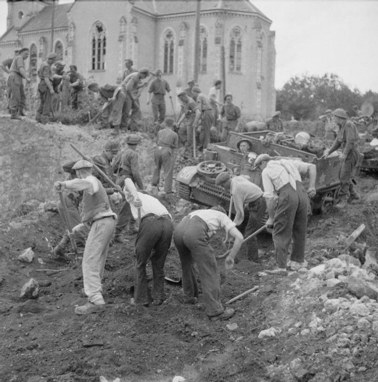 French civilians assist British troops to clear a road for a carrier near L'Aigle, 23 August 1944.