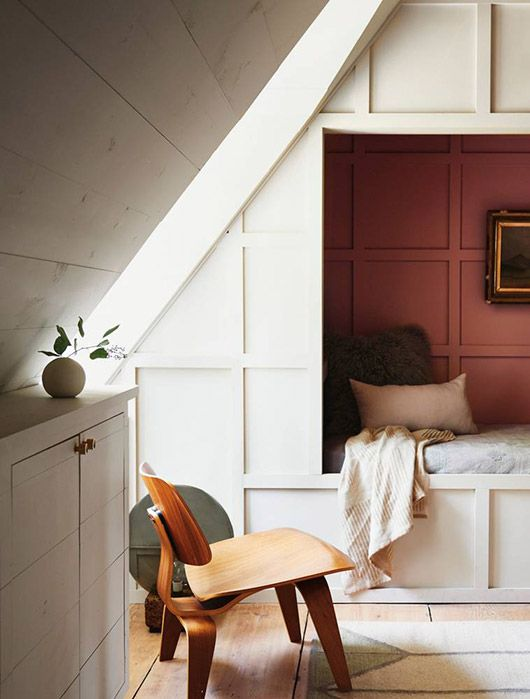 Cozy nook under a roof slope with a wooden chair, some wool blankets and pillows. We love the pink wall and the white wall paneling.
