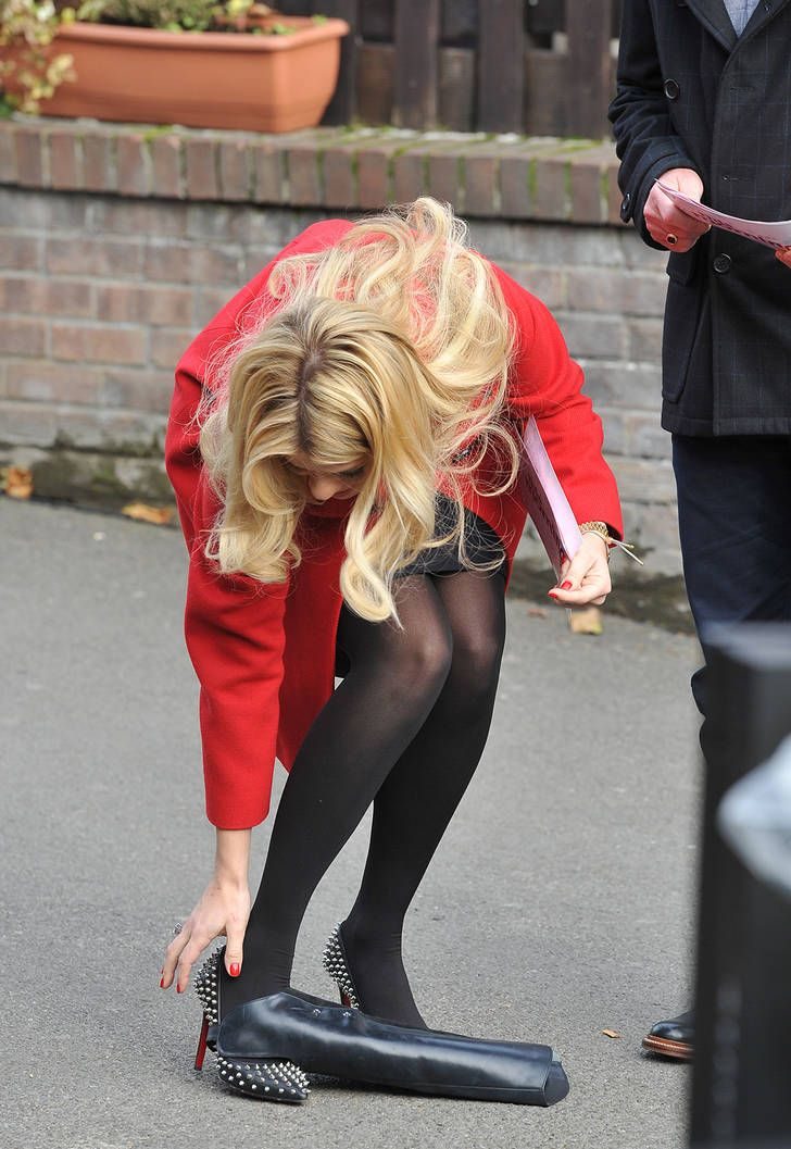 Holly Willoughby in black tights, bright red coat and studded heels picking up her clutch bag | Pantyhose Party