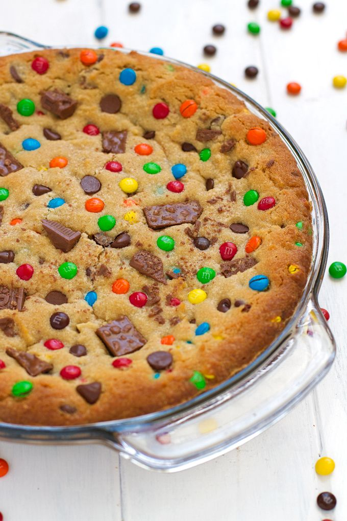 M&M loaded chewy chocolate chip cookie cake recipe that's perfect to serve for birthdays! Cookie cake is soft in the center with a chewy, crunchy crust.