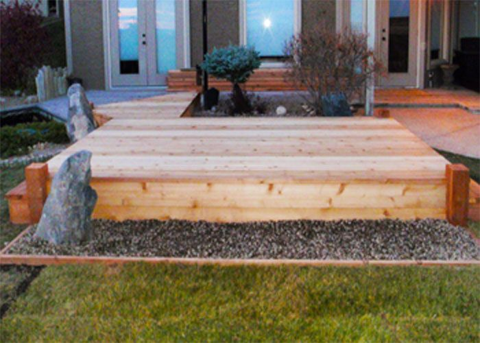 CREATE ESCAPE - Edgemont.  Japanese style on gorund cedar deck with decorative 6x6 cedar posts. Plantings, Rundle gravel and  accent boulders help to create the theme. Simple design with lots of impact.